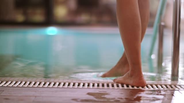 woman enters swimming pool at health spa - poolside stock videos & royalty-free footage