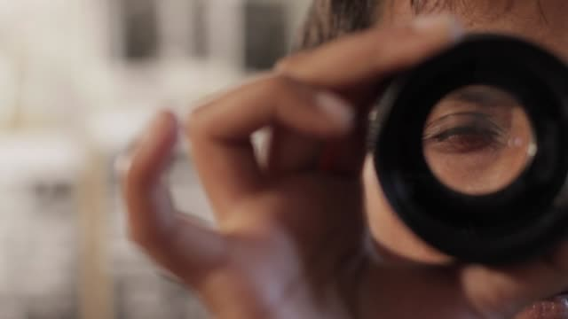 A woman examines a photo lens up close and personal