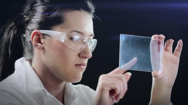 vídeos de stock, filmes e b-roll de woman examines sample demo - bolha de replicação