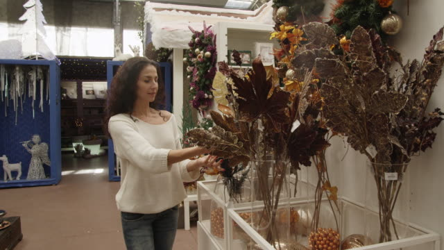 MS woman examining artificial flowers on display in store