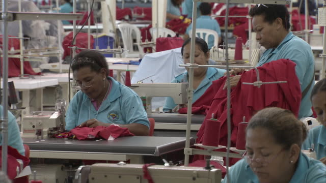 MS ZO WS Woman examining finished garments, standing by workers at sewing factory/ Cabimas, Zulia, Venezuela