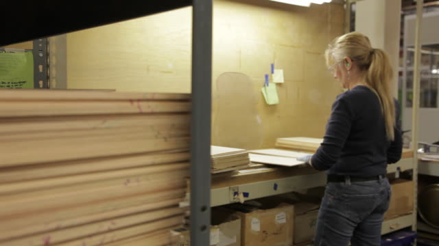 MS PAN Woman examining flat wood boards in guitar factory / Nazareth, Pennsylvania, USA