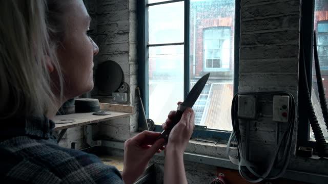 woman examining knife - mid length hair stock videos & royalty-free footage