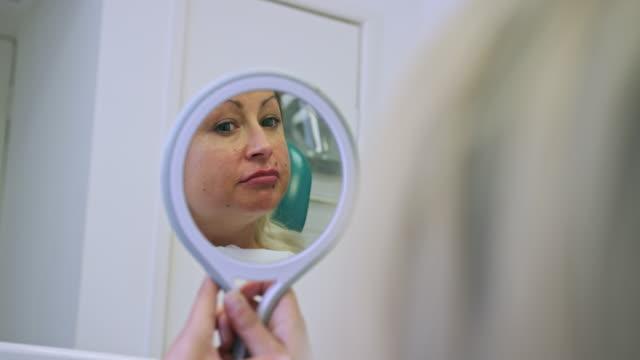 woman examining lips - イーストサセックス点の映像素材/bロール