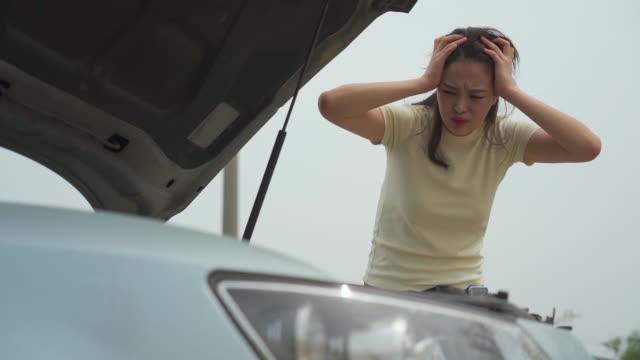 vidéos et rushes de woman examining the car engine - seulement des jeunes femmes