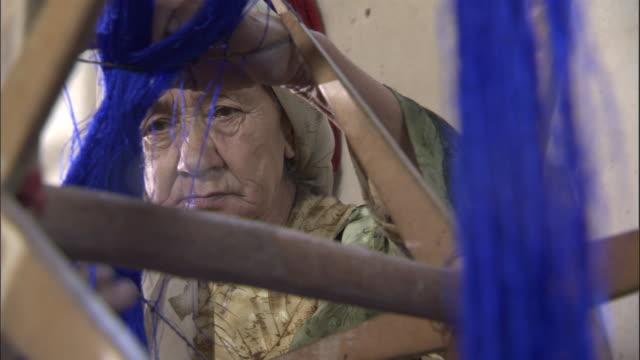 Woman exams blue silk on wooden frame, Hetian, Xinjiang, China