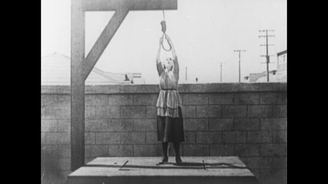 1920 woman exchanges noose rope with spring weights - galgen stock-videos und b-roll-filmmaterial