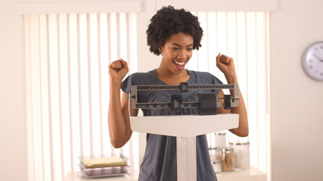 woman excited about weight loss on scale - dieting stock videos & royalty-free footage