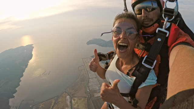 pov di donna entusiasta nel suo primo sky dive in tandem - avventura video stock e b–roll
