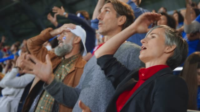 Woman excitedly cheering with raised hands but lowering them disappointed at the score