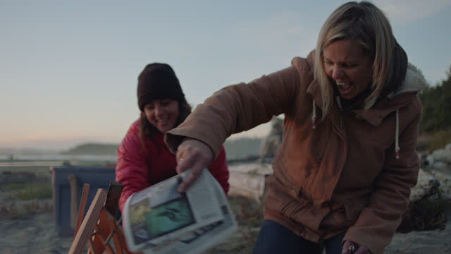 SLO MO. Woman excitedly fans campfire with a newspaper as friend laughs on the beach at sunset.