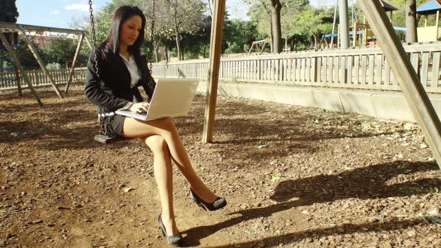 woman executive networking in park on swing set - minigonna video stock e b–roll