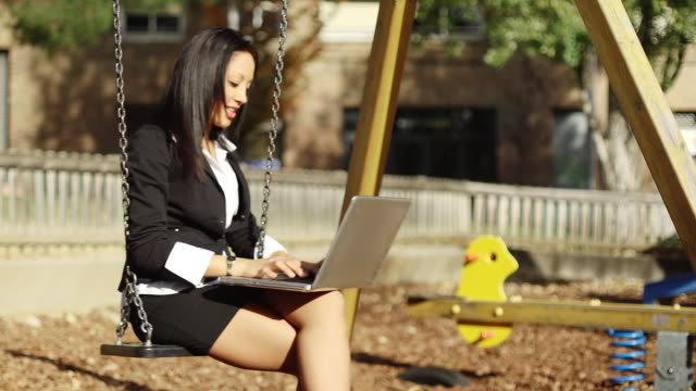 Woman executive networking in park on swing