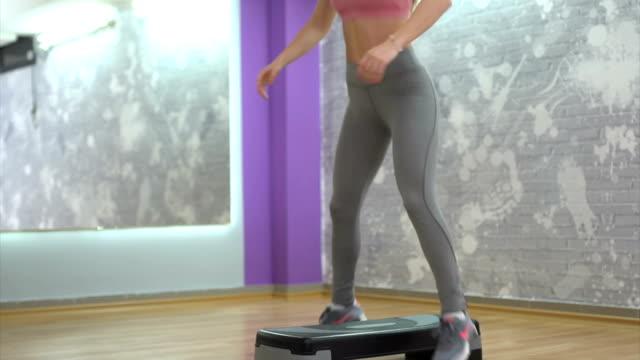 woman exercises on aerobic stepper - step aerobics stock videos & royalty-free footage