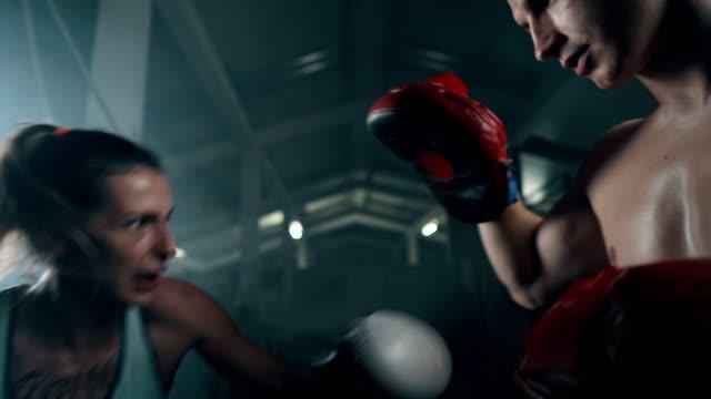 vídeos de stock, filmes e b-roll de mulher se exercita com parceiro de luta - posição de combate