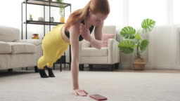 Woman exercising and using mobile phone at home