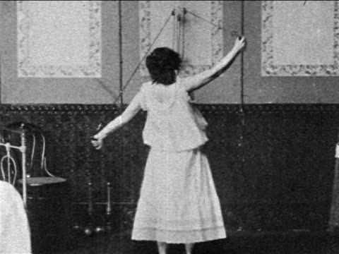 b/w 1903 woman exercising arms indoors with wall-mounted weights / newsreel - 1903 stock-videos und b-roll-filmmaterial
