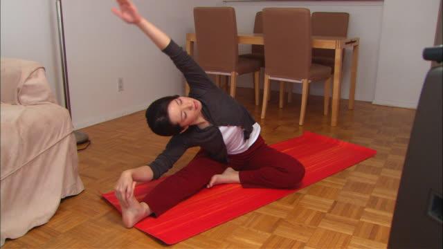 ms, woman exercising at home - full length点の映像素材/bロール