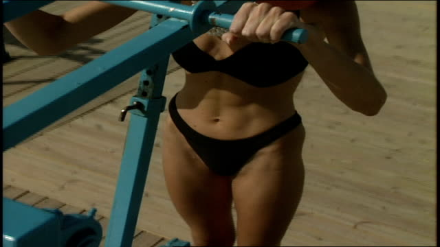 Woman Exercising in a Swimsuit Sunglasses and Pearls in Miami Florida