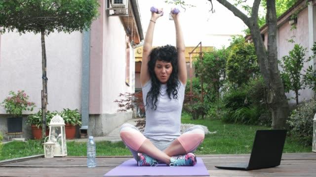 vídeos y material grabado en eventos de stock de mujer haciendo ejercicio en jardín formal - formal garden