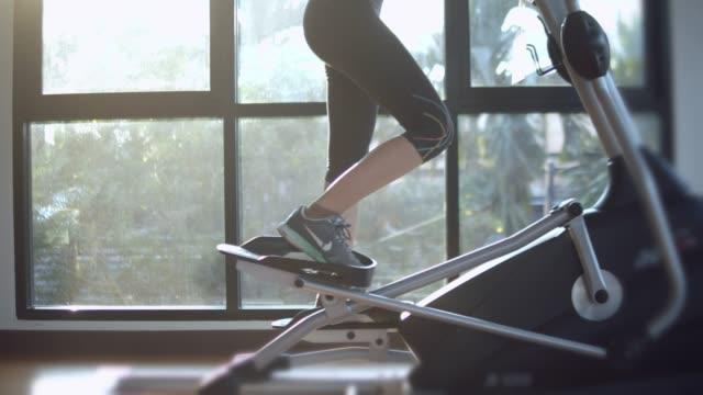 女性のカーディオ マシンでエクササイズ - ウェイトトレーニング用器具点の映像素材/bロール