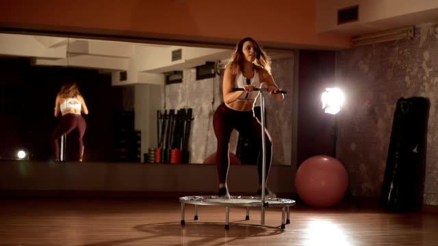 ジムでミニ トランポリン運動の女性 - トランポリン点の映像素材/bロール
