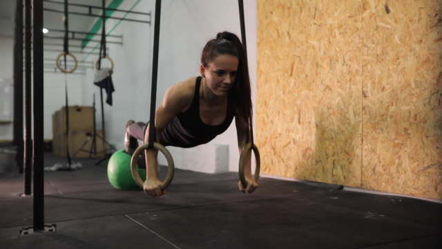 woman exercising on gymnastic rings - gymnastic rings stock videos & royalty-free footage