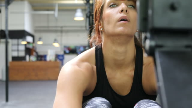woman exercising on rowing machine in gym - rowing machine stock videos & royalty-free footage