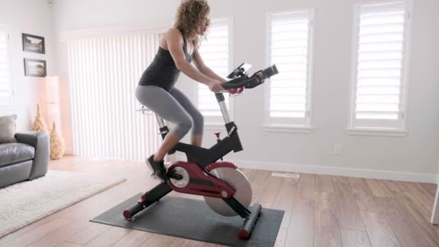 woman exercising on spin bike in home - cardiovascular exercise stock videos & royalty-free footage