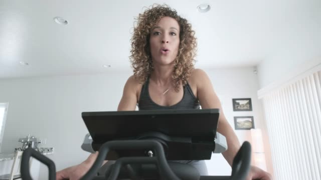 woman exercising on spin bike in home - stationary stock videos & royalty-free footage