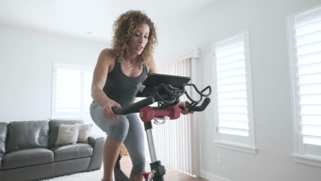woman exercising on spin bike in home - exercise equipment stock videos and b-roll footage