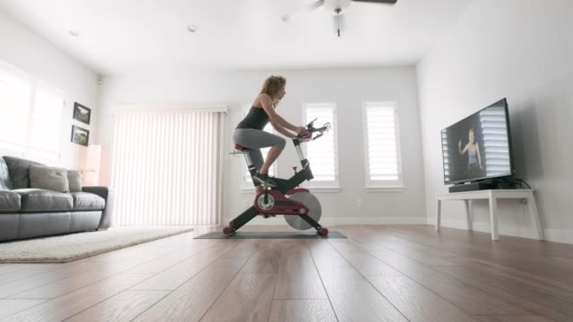 woman exercising on spin bike in home - indoors stock videos & royalty-free footage