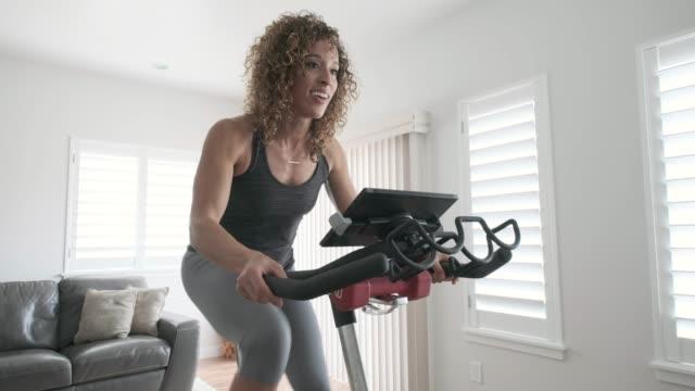 vídeos de stock, filmes e b-roll de mulher exercitando na bicicleta spin em casa - equipamento para exercícios