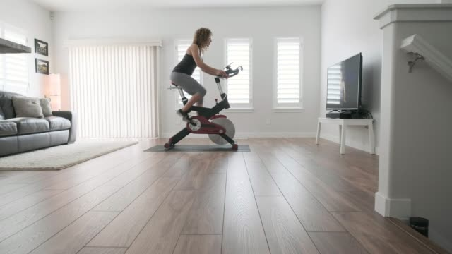 woman exercising on spin bike in home - net sports equipment stock videos & royalty-free footage