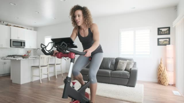 woman exercising on spin bike in home - exercise bike stock videos & royalty-free footage