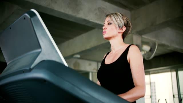 stockvideo's en b-roll-footage met vrouw uit te oefenen op loopband - jogster