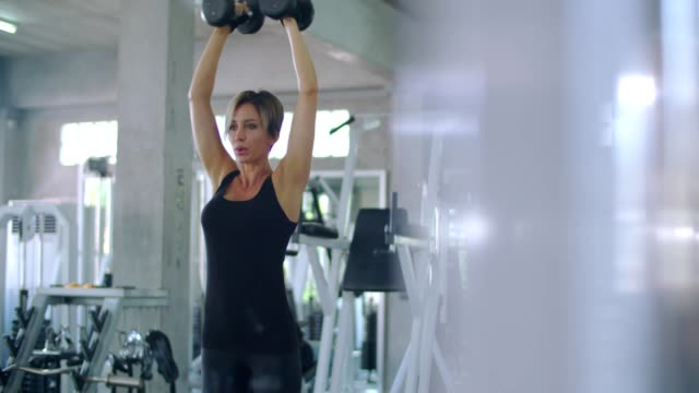Woman exercising with dumbbell weights in gym