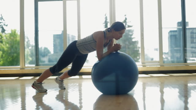 ws woman exercising with fitness ball in gym / vancouver, british columbia, canada - pallone per fitness video stock e b–roll