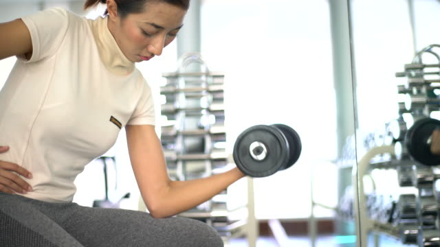 Woman exercising With Weights in fitness room