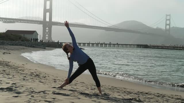 woman exercising yoga at a beach near san francisco's golden gate bridge - full length stock videos & royalty-free footage