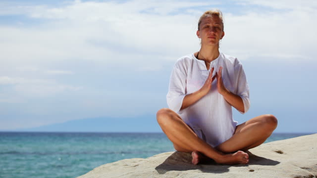 hd: woman exercising yoga at the beach - lotus position stock videos & royalty-free footage
