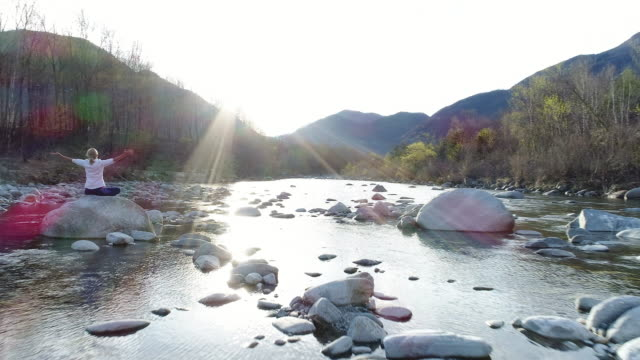 woman exercising yoga by the river - lotus position stock videos & royalty-free footage
