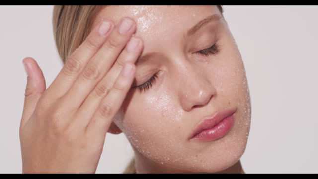 woman exfoliates face with both hands - scrubbing stock videos & royalty-free footage