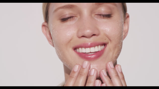 Woman exfoliates face with both hands