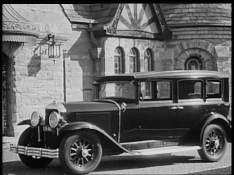 b/w 1928 woman exiting buick in front of fancy house / industrial - 1928 stock-videos und b-roll-filmmaterial