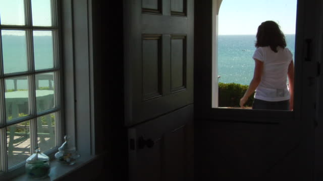 CU, Woman exiting cottage, facing ocean and coming back, North Truro, Massachusetts, USA