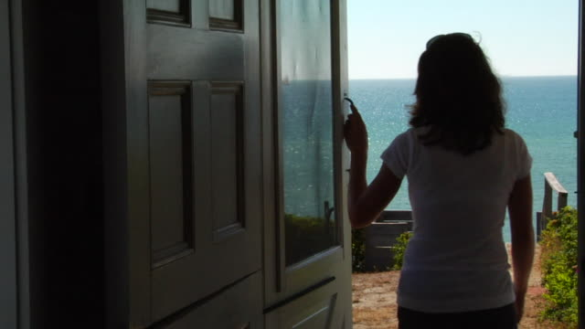 cu, woman exiting cottage, facing ocean and coming back, north truro, massachusetts, usa - cottage stock videos & royalty-free footage