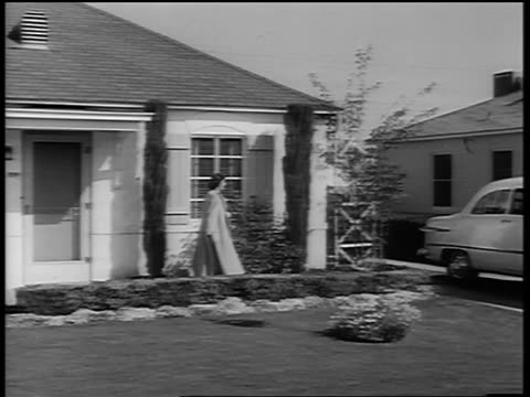 B/W 1950 PAN woman exiting suburban house + walking to car / two boys run to car from behind house