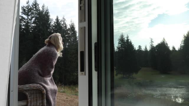 frau verlässt tür veranda, sonnenaufgang-uhren - one mature woman only stock-videos und b-roll-filmmaterial