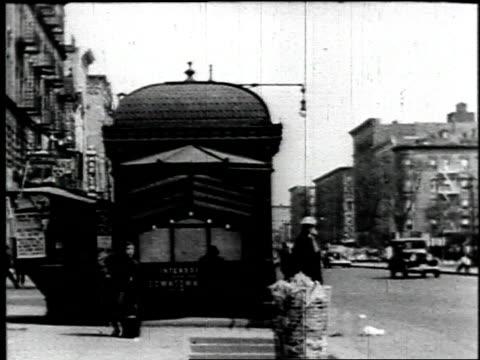 1940 B/W Woman exits subway onto sidewalk in Harlem, looks at pamphlet, city street, many pedestrians / New York City